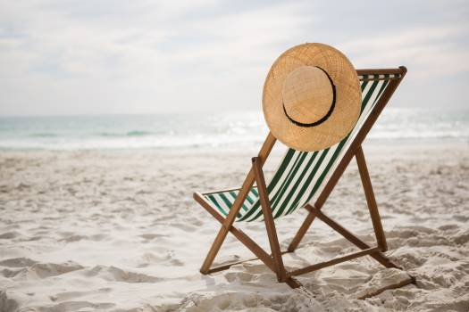 Straw hat kept on empty beach chair #412062