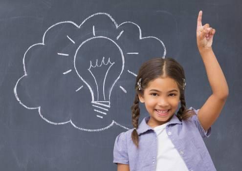 Schoolgirl raising her hand in front of a blackboard #412088