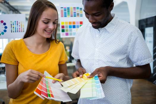 Male and female graphic designers choosing color from the sampler #412096