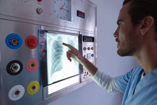 Male surgeon examining x-ray on x-ray light box in operation room at hospital #412101