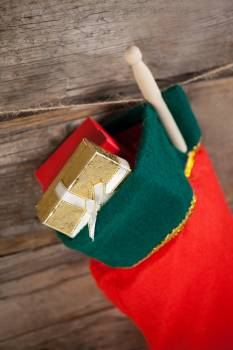 Christmas stocking with present box hanging against wooden wall Free Photo