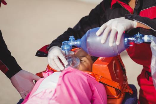 Paramedic giving oxygen to injured girl #412136