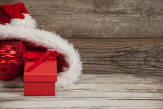 Close-up of red Christmas bauble and gift kept in santa hat #412200