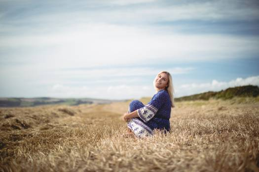 Blonde woman sitting in field #412202