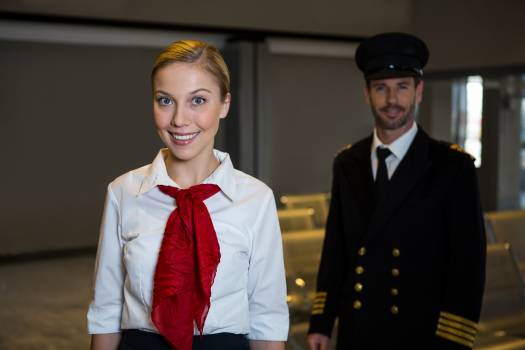 Happy pilot and Air hostess standing in the airport terminal #412209