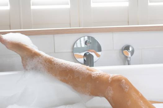 Woman taking bubble bath in bathroom at home Free Photo