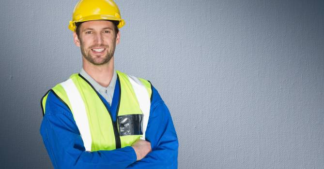 Construction worker standing with his arms crossed against grey background #412234