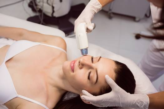 Dermatologist giving facial massage through soniclifting Free Photo