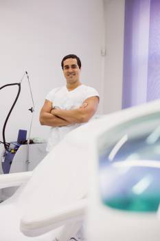 Smiling doctor standing with arms crossed Free Photo