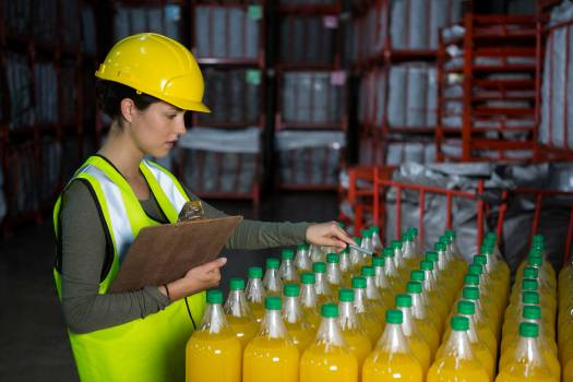 Female worker examining juice bottles #412265
