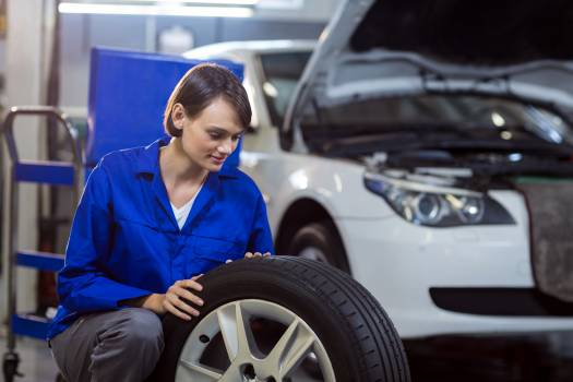 Female mechanic checking a tyre #412287