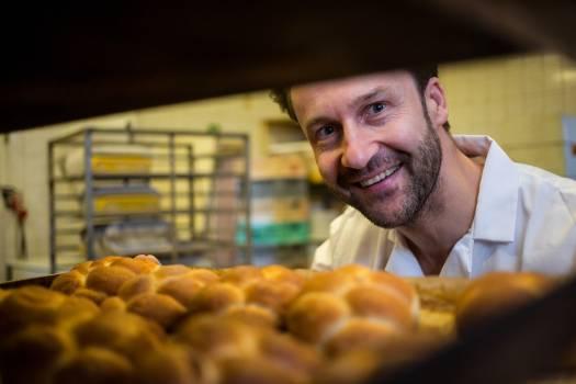 Smiling baker removing baked bun from oven #412307
