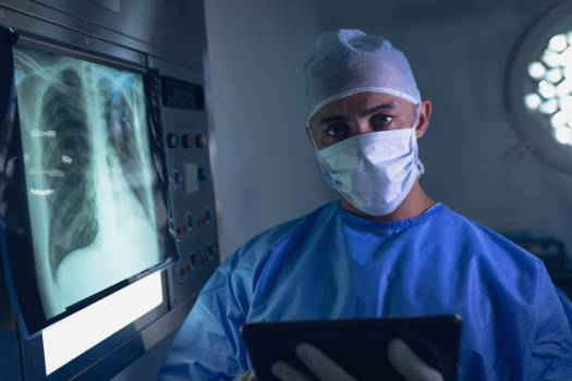 Male surgeon examining x-ray report on digital tablet in operating room #412325