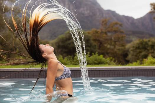 Woman flipping her hair in swimming pool #412333