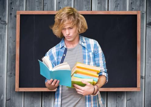Teenage student reading books against blackboard #412338