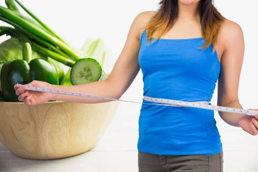 Midsection of woman measuring waist against vegetables in background #412362