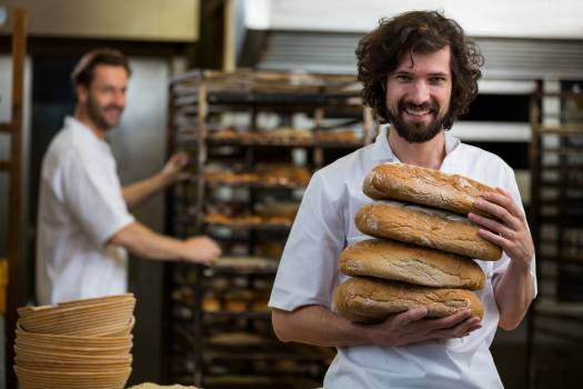 Smiling baker carrying stack of baked breads #412374