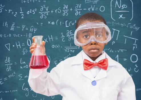 Boy wearing protective glasses holding a beaker against black board #412392