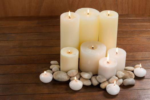 Close- up of white candles and pebbles stone on wood Free Photo