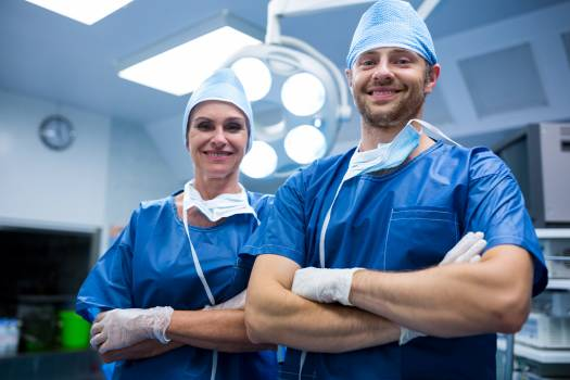 Portrait of surgeons standing with arms crossed in operation room Free Photo