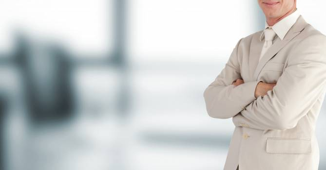 Happy business man with beige suit on blurred background Free Photo