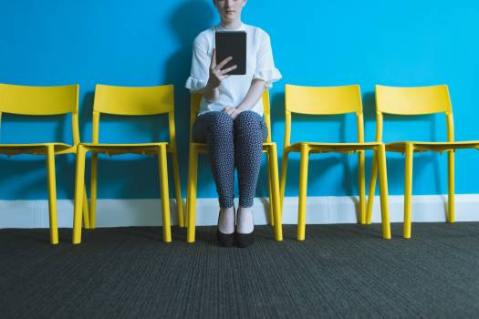 Female executive sitting on chair and digital tablet Free Photo