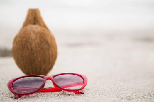Coconut and a sunglass kept on the sand #412527