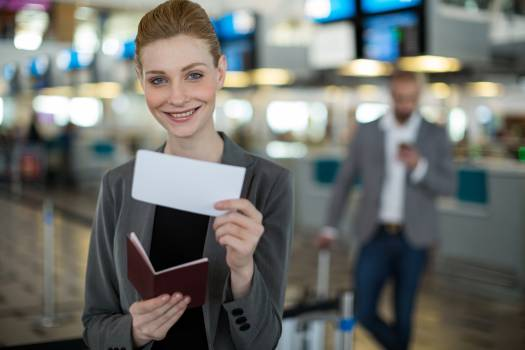 Portrait of smiling businesswoman showing her boarding pass Free Photo