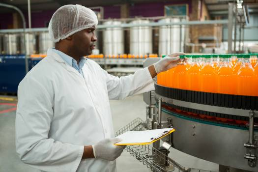 Male worker examining bottles in juice factory #412568