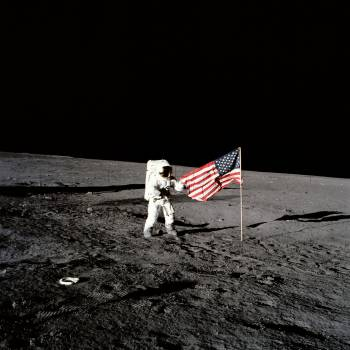 Apollo 12 astronaut stands beside United States flag after is was unfurled #412584