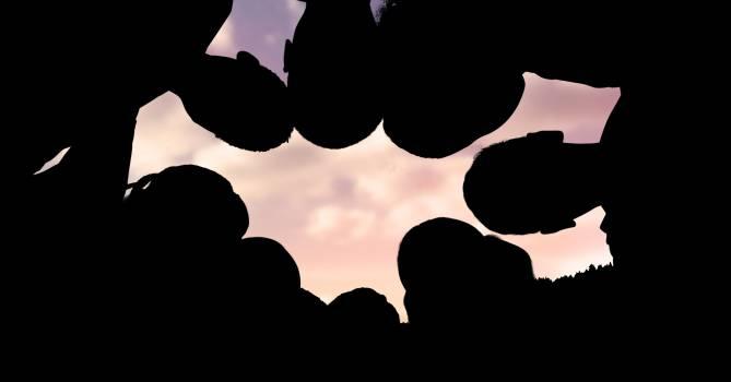 Silhouette children making huddle against sky #412589