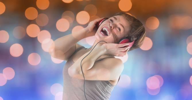 Happy music artist wearing headphones over bokeh #412593