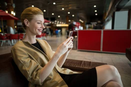 Businesswoman using mobile phone in waiting area Free Photo