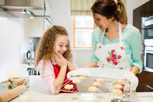 Mother interacting with daughter while holding cookies in cooling rack Free Photo
