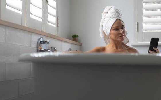 Woman using mobile phone while sitting in bathtub at home #412626