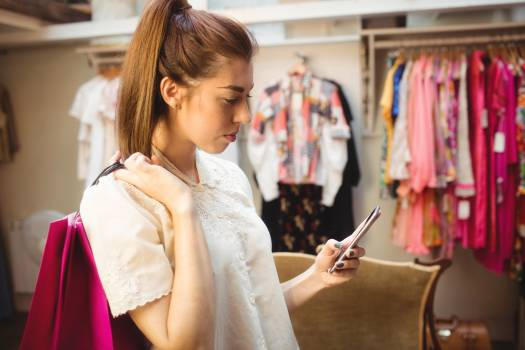 Woman using mobile phone while shopping Free Photo
