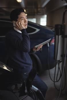 Man talking on mobile phone while charging electric car #412640