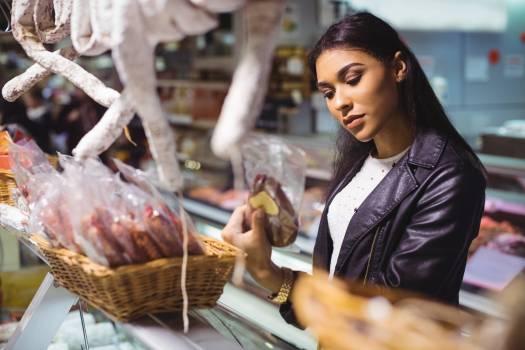 Woman selecting sausage at meat counter #412649