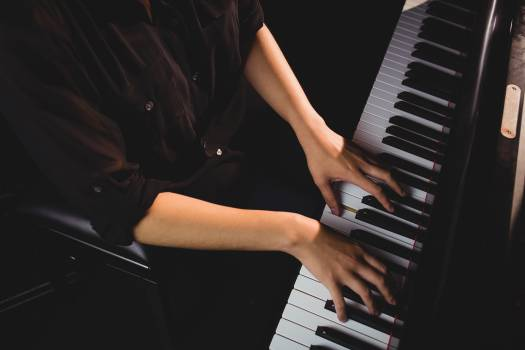 Mid-section of female student playing piano #412667