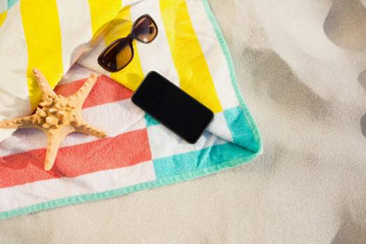 Starfish, sunglasses and mobile phone kept on beach blanket #412689