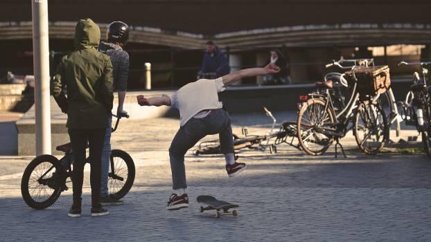 Man in White Shirt Doing Skateboard Trick #41268