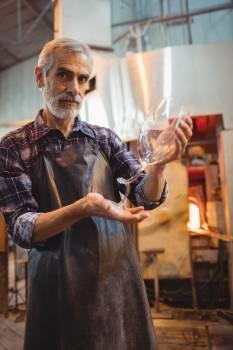 Glassblower holding glassware Free Photo
