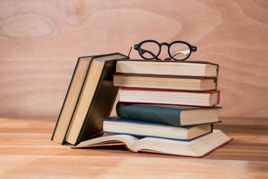 Various books with spectacles on a table #412700