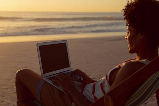 Man using laptop while relaxing in a beach chair on the beach #412705