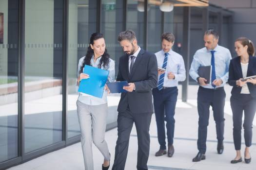 Group of business people walking outside office building Free Photo