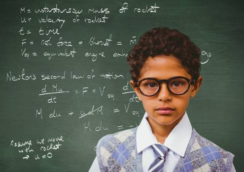 Portrait of boy in spectacles standing against scientific formula on chalkboard #412780