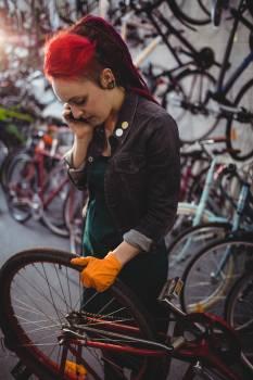 Mechanic talking on mobile phone while repairing bicycle #412782
