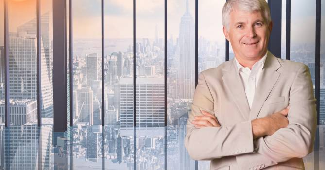Businessman standing with arms crossed against cityscape in background #412810