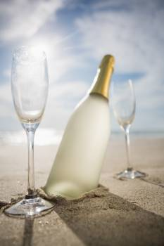 Champagne bottle and two glasses on sand #412830