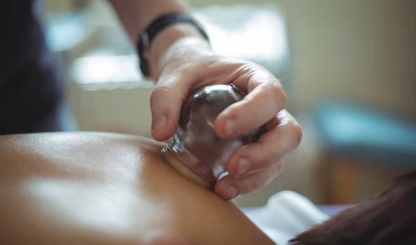 Close-up of therapist giving cupping therapy to man Free Photo